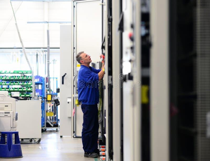 Mannen monterar elektroniska delar på en maskin i en fabrik fo royaltyfri foto
