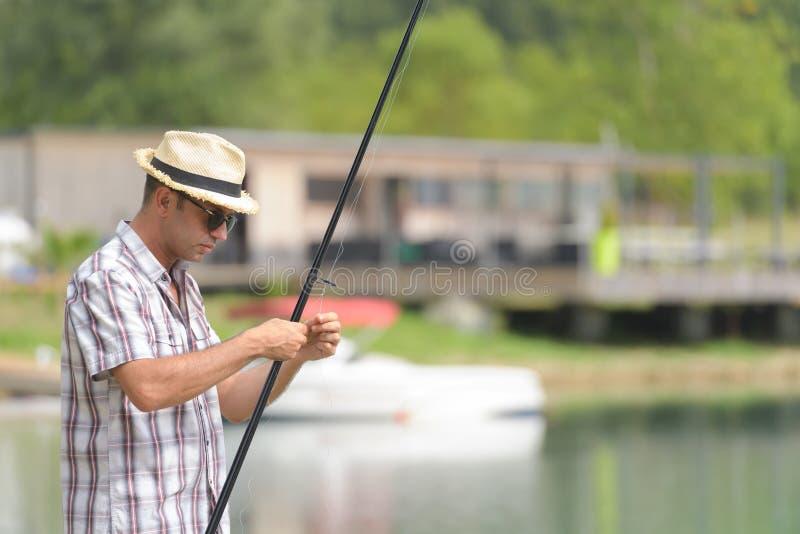 Mannen nära sjön förbereder sig för fångstredskap arkivbild