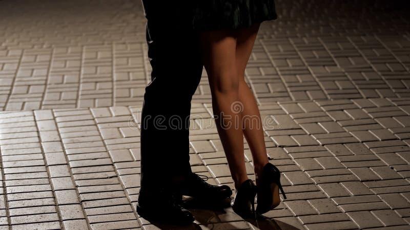 Mannen och den kvinnliga dansen och att tycka om det romantiska datumet, aftontid, ben stänger sig upp arkivfoton