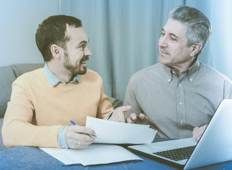 Mannen och försäljningschefen diskuterar avtalet royaltyfri fotografi