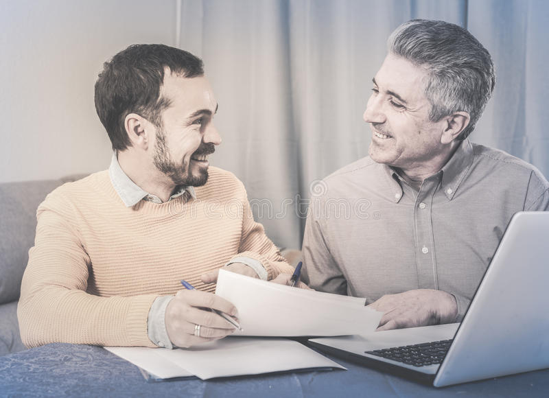 Mannen och försäljningschefen diskuterar avtalet arkivfoton