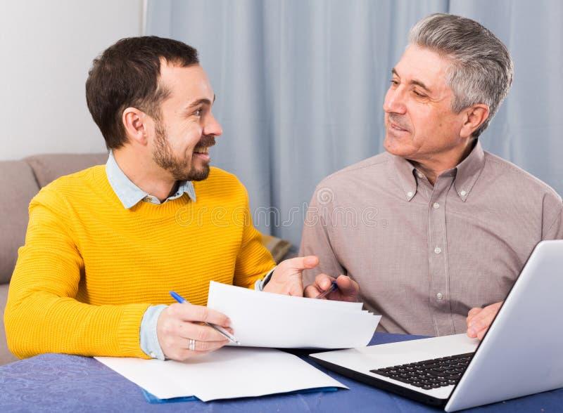 Mannen och försäljningschefen diskuterar avtalet royaltyfria bilder