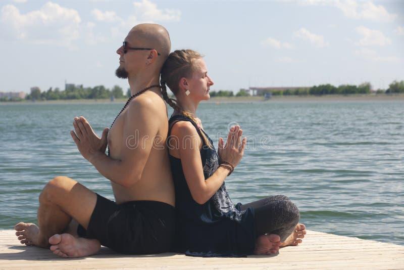 Mannen och gravida kvinnan g?r yoga p? stranden royaltyfri fotografi
