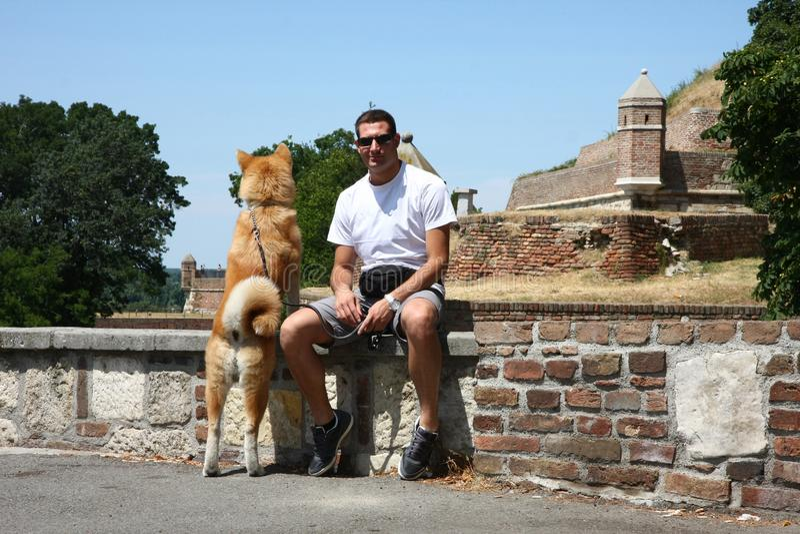 Mannen och hunden parkerar offentligt royaltyfri fotografi
