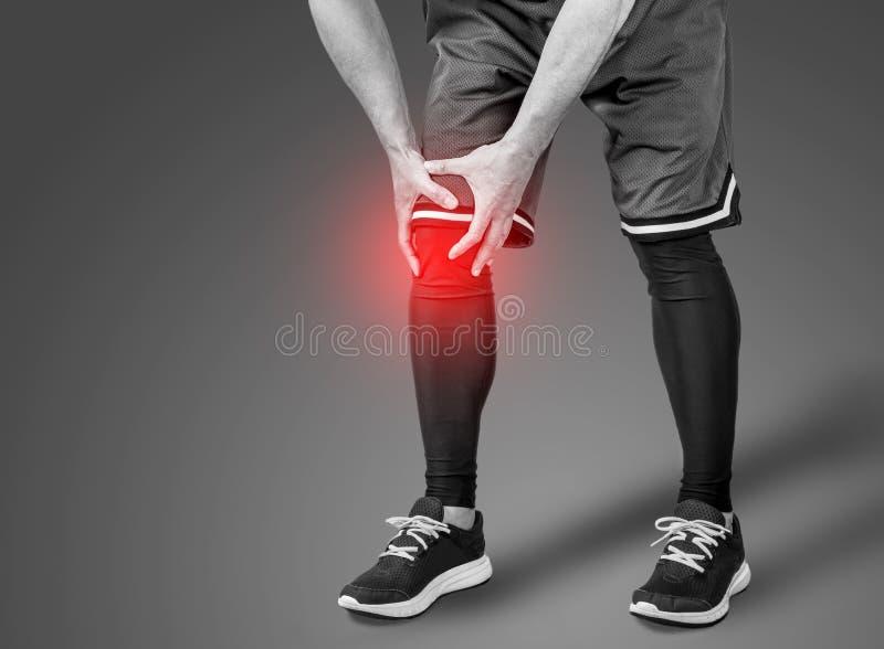 Mannen och knäet smärtar royaltyfri bild