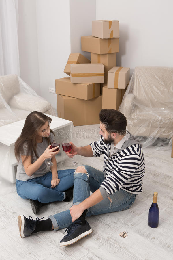 Mannen och kvinnan är lyckliga att fira förflyttning till den nyligen hyrda lägenheten royaltyfri fotografi