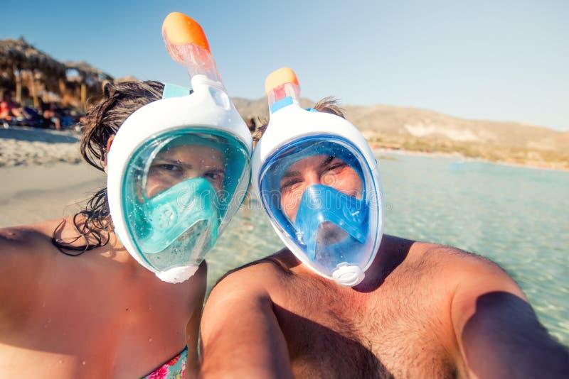 Mannen och kvinnan, barn kopplar ihop i semester och att ta selfie med den undervattens- kameran, att snorkla och att le royaltyfri foto