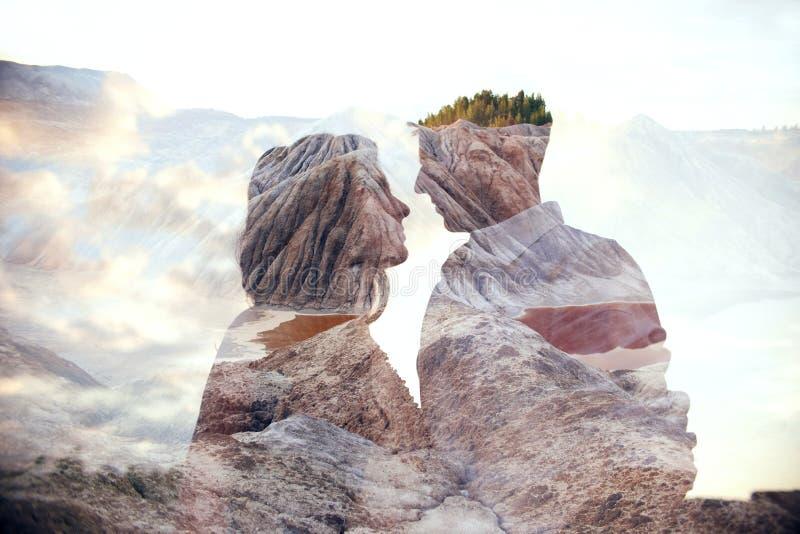 Mannen och kvinnan för dubbel exponering kopplar ihop att krama med berg i bakgrund Förälskade berginsidapar Vänblick på varje royaltyfri bild