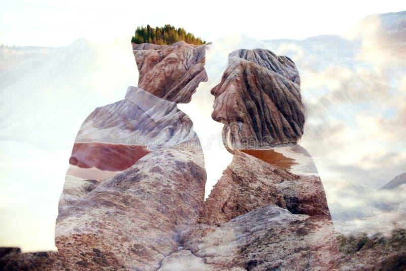 Mannen och kvinnan för dubbel exponering kopplar ihop att krama med berg i bakgrund Förälskade berginsidapar Vänblick på varje arkivbilder