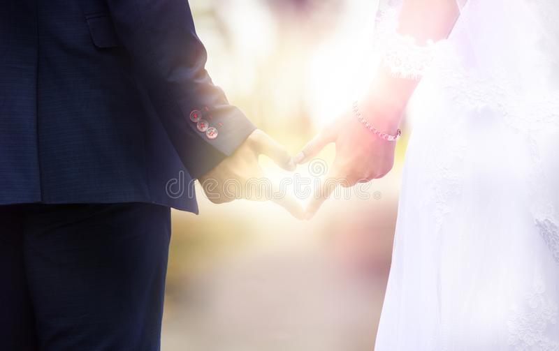 Mannen och kvinnan gör hjärta med deras händer royaltyfri bild