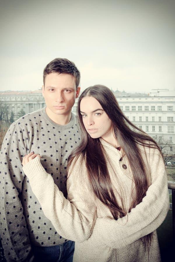 Mannen och kvinnan, i att omfamna, poserar på utvändig balkong arkivfoton