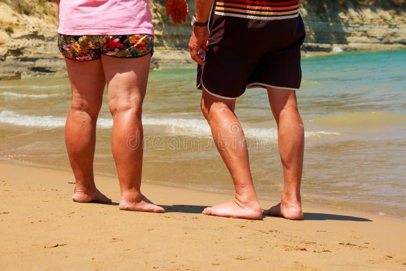 Mannen och kvinnan i kortslutningar som går på havet, sätter på land solig dag för sommar Semester på havet avgångtid Gamla männi arkivfoto