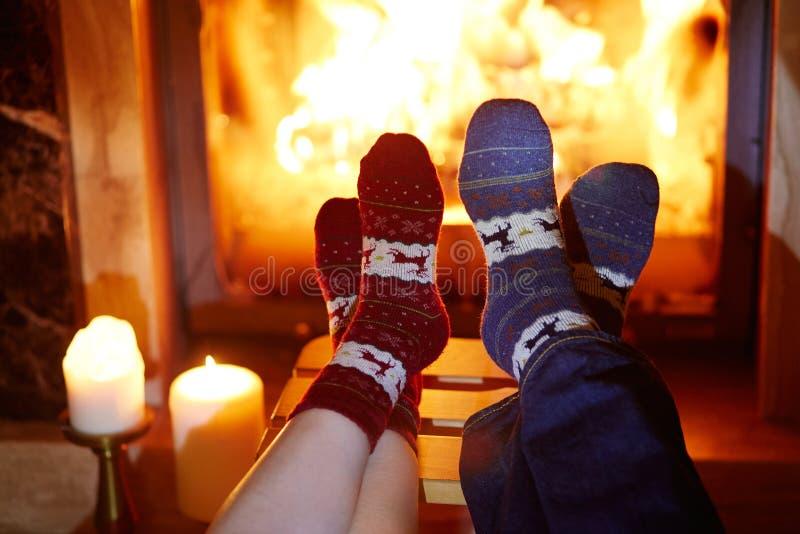 Mannen och kvinnan i varma sockor near spisen arkivbilder