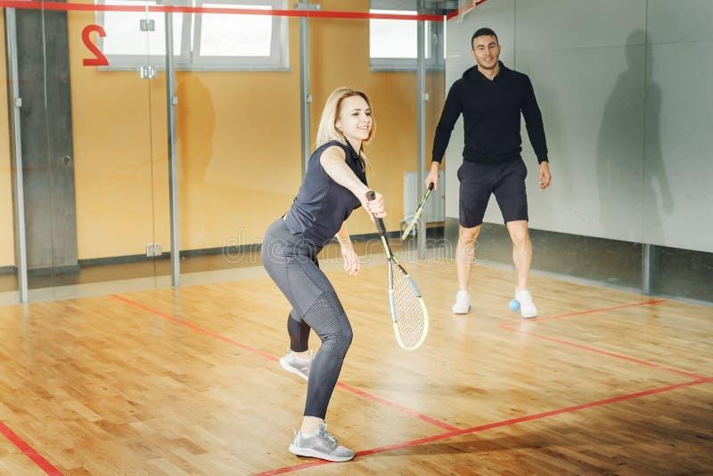 Mannen och kvinnan konkurrerar i en squashlek ung grabb- och flickahållracket arkivfoton