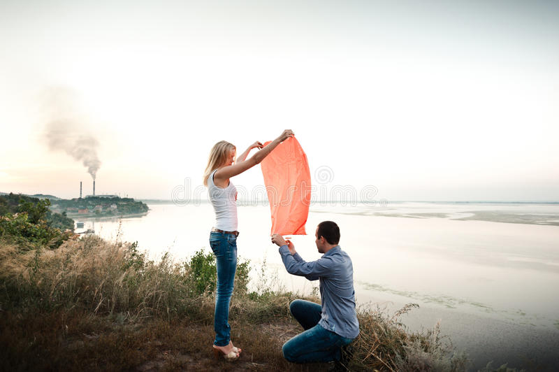 Mannen och kvinnan lanserar en hjärta formad ficklampa i himlen arkivfoton