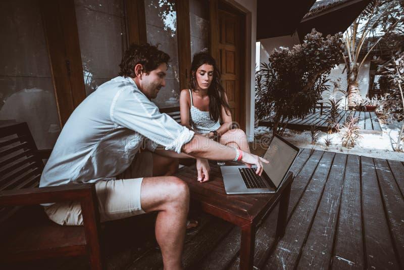 Mannen och kvinnan med bärbara datorn på huset terrasserar royaltyfri foto