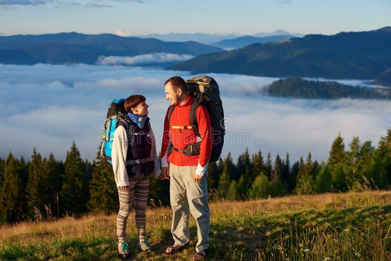 Mannen och kvinnan med ryggsäckar ser de i strålar av solnedgången mot berg arkivbild