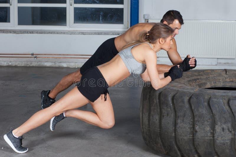 Mannen och kvinnan på en utbildning för gummihjulcrossfitkondition värmer upp arkivfoton