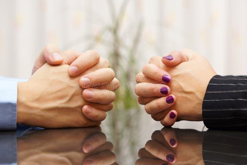 Mannen och kvinnan sitter på ett skrivbord med knäppte fast händer äktenskapligt problem royaltyfri fotografi
