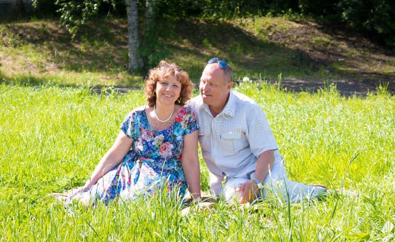 Mannen och kvinnan sitter på gräset royaltyfria foton