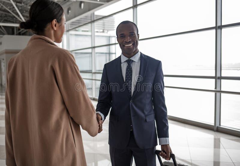 Mannen och kvinnan skakar händer med leende royaltyfri foto