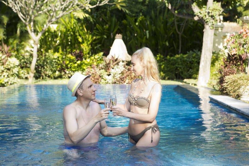 Mannen och kvinnan som älskar par, i pöl i en trädgård med tropiska träd, rymmer exponeringsglas med vin i hand royaltyfria bilder