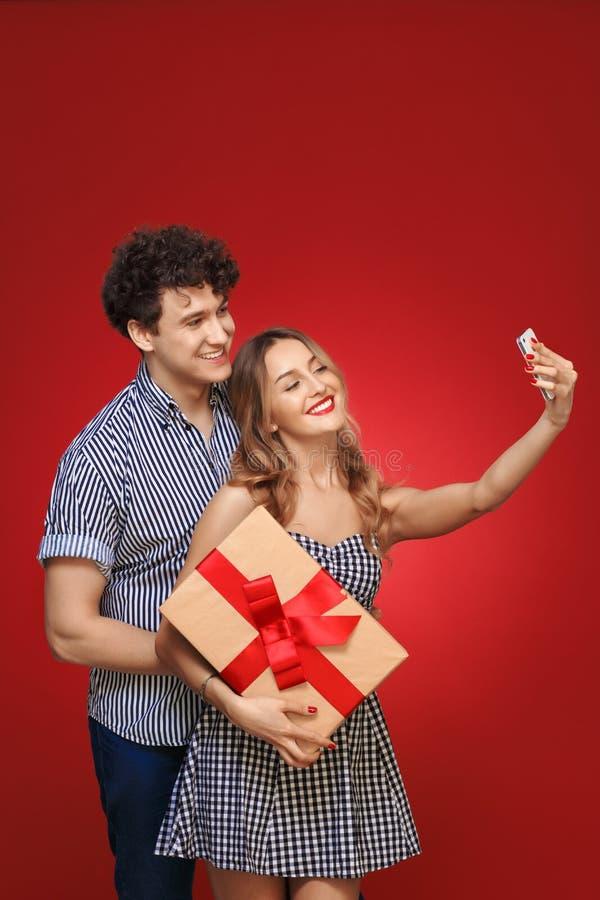Mannen och kvinnan som gör selfie, ringer Pin Up med en gåva i stil, är royaltyfria foton