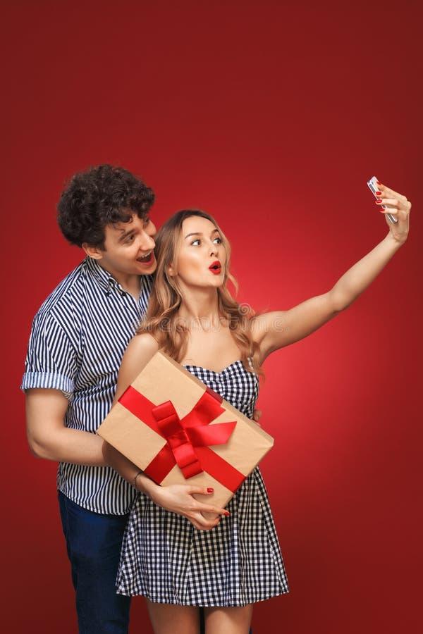 Mannen och kvinnan som gör selfie, ringer Pin Up med en gåva i stil, är fotografering för bildbyråer
