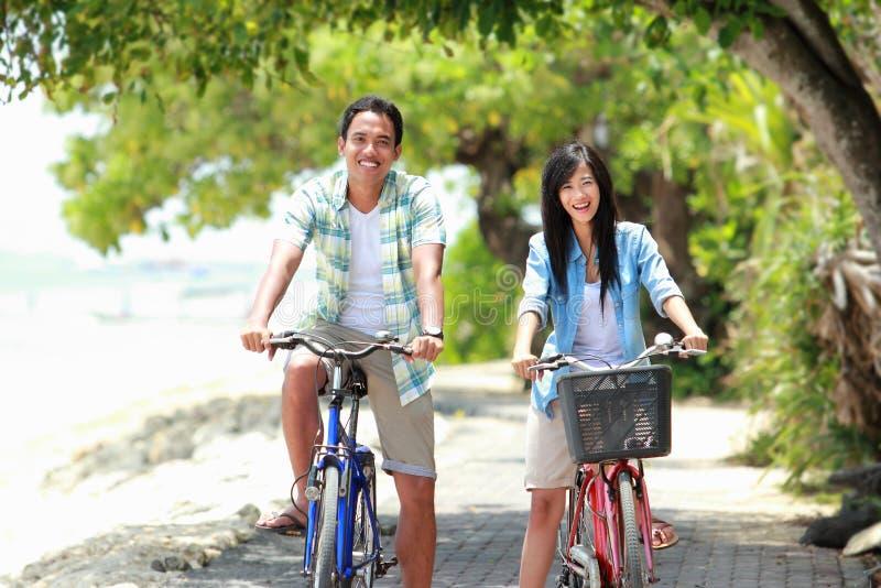 Mannen och kvinnan som har rolig ridning, cyklar tillsammans arkivbild