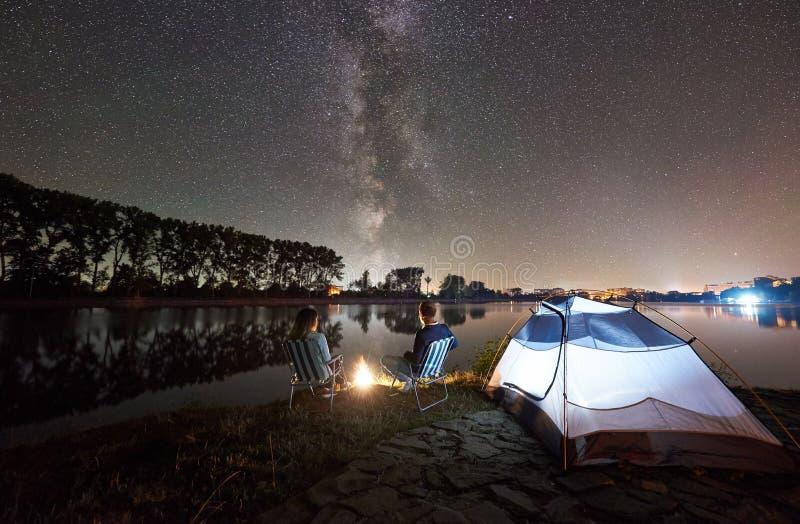Mannen och kvinnan som har, vilar p? kust under natthimmel arkivfoto
