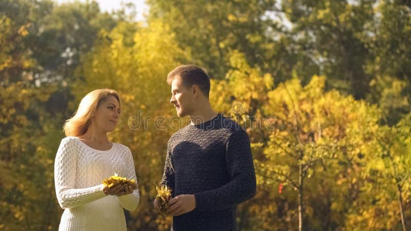 Mannen och kvinnan som rymmer och förbereder sig att kasta gula sidor och att ha gyckel parkerar in royaltyfria foton