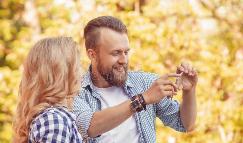 Mannen och kvinnan som tar foto med en kamera och en smartphone i höst, parkerar royaltyfri bild