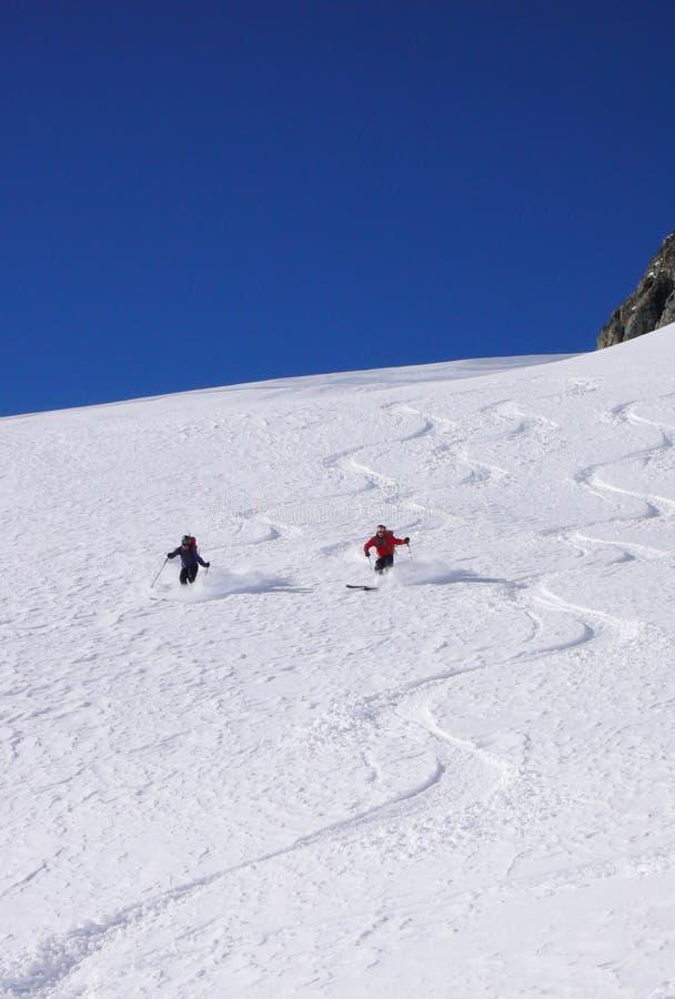 Mannen och kvinnliga backcountry skidåkare drar första spår i det insnöade nya pulvret fjällängarna royaltyfri bild