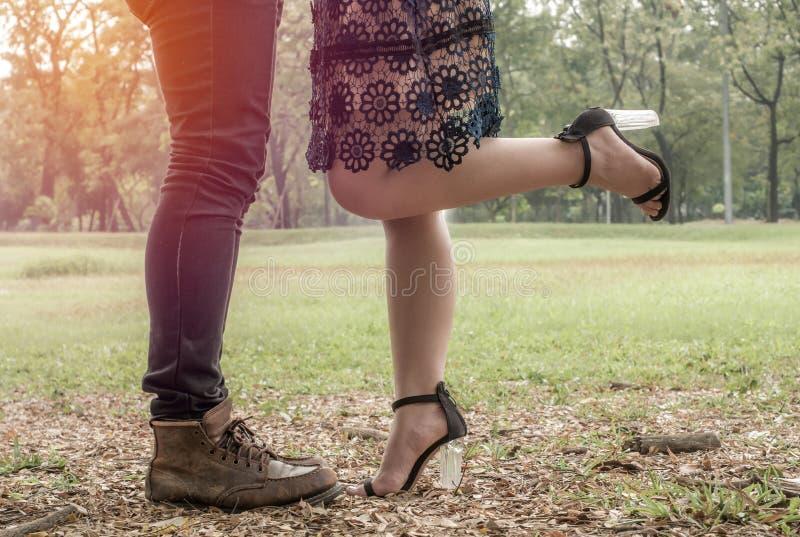 Mannen och kvinnliga ben under ett datum i parkerar, förälskelsebegreppet royaltyfria bilder