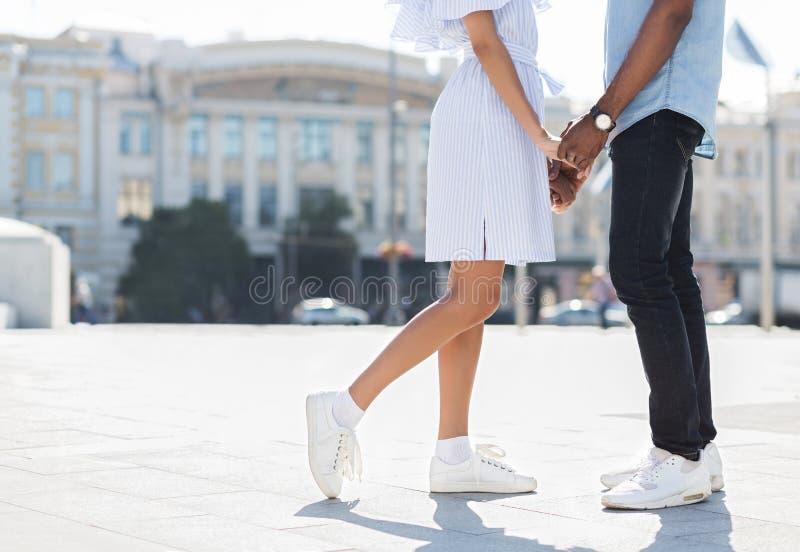 Mannen och kvinnlign lägger benen på ryggen under datum i stad arkivfoton