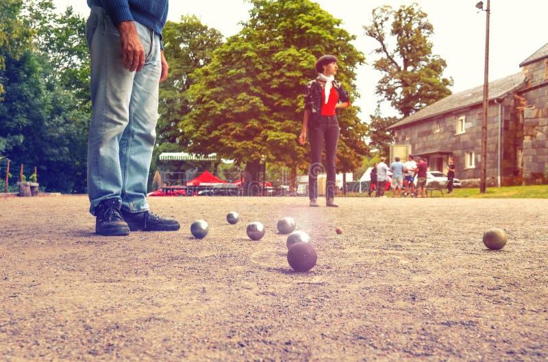 Mannen och kvinnlign som spelar petanque i th, parkerar på ferier arkivfoto