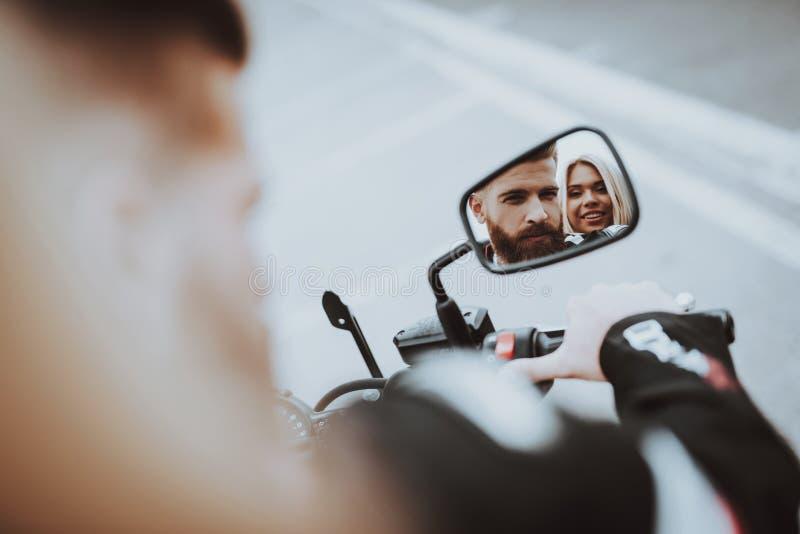 Mannen och kvinnor stirrar i en cykelbackspegel arkivfoto