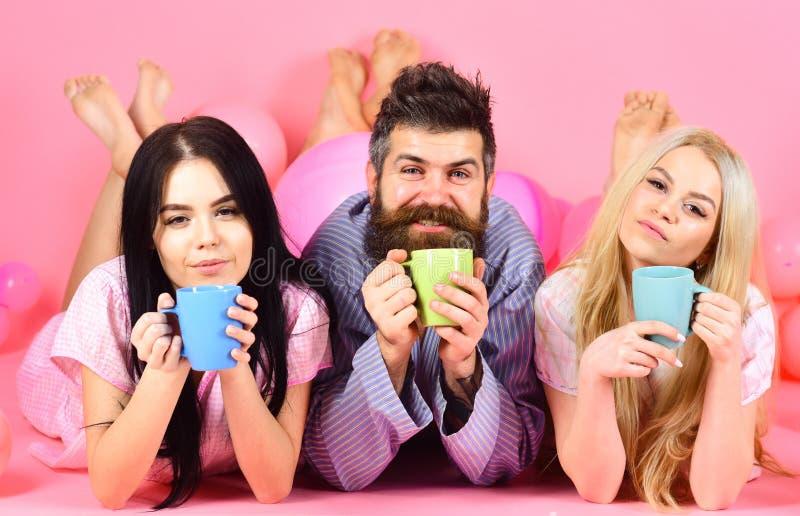 Mannen och kvinnor, vänner på sömniga framsidor lägger, rosa bakgrund Vänner som dricker kaffe i säng Threesomen kopplar av i mor arkivfoto