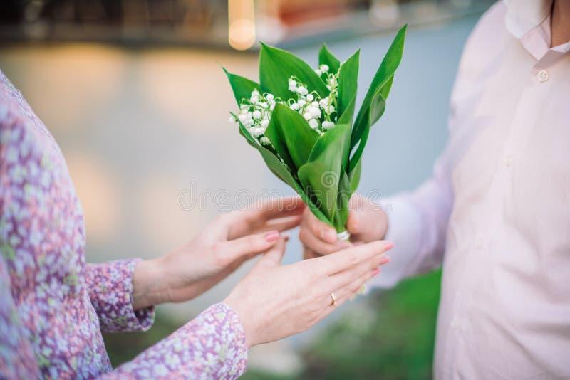 Mannen och woman räcker med liten bukett av liljan dalen fotografering för bildbyråer