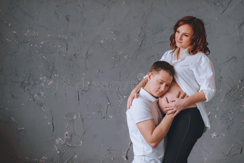 Mannen omfamnar magen av en gravid kvinna Det finns ett ställe för Tex på en grå färgbakgrund Hon ser bort fotografering för bildbyråer
