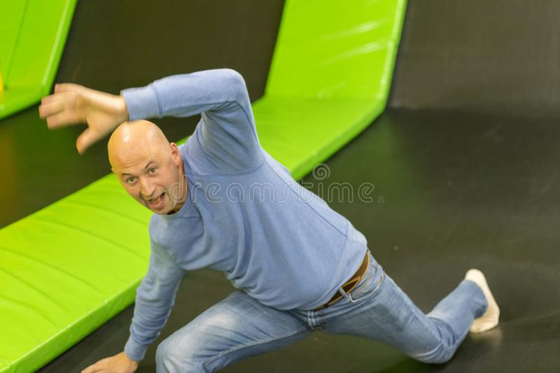 Mannen på en trampolin Mannen avverkar på en trampolin Första gång för man på trampolinen arkivfoto