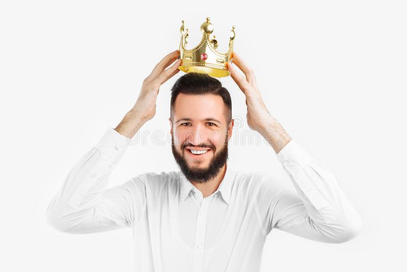 Mannen på en vit bakgrund bär en krona på hans huvud, i en fotostudio arkivbilder