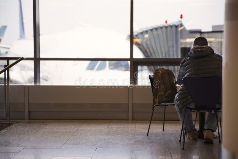 Mannen på flygplatsen sitter och väntar på att stiga ombord nivån royaltyfria bilder