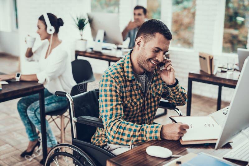 Mannen på rullstolen skriver anmärkningar och samtal på telefonen royaltyfri foto