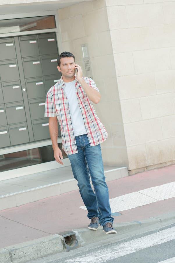 Mannen på telefonen verkar borttappad royaltyfria foton