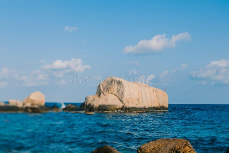 Mannen på vaggar ska hoppa in i havet Vagga i det blåa havet och ett moln i himlen Koh Tao strand i Thailand arkivfoto