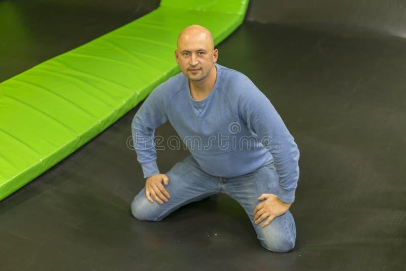 Mannen p? en trampolin Mannen avverkar p? en trampolin F?rsta g?ng f?r man p? trampolinen arkivbilder