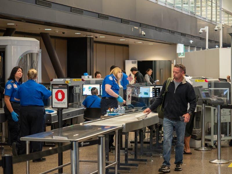 Mannen passerar fast testpunktet för säkerhet för trans.säkerhetsadministrationen TSA på Seattle-Tacoma den internationella flygp royaltyfria foton