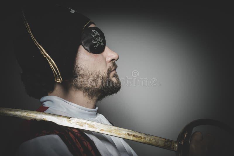 Mannen piratkopierar med ögonlappen och den gamla hatten med roliga framsidor och expre royaltyfria foton