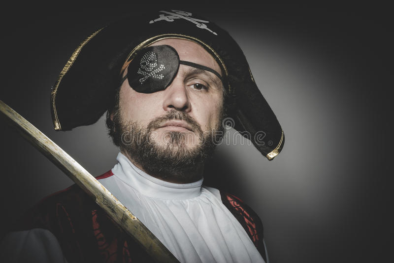 Mannen piratkopierar med ögonlappen och den gamla hatten med roliga framsidor och expre arkivfoto